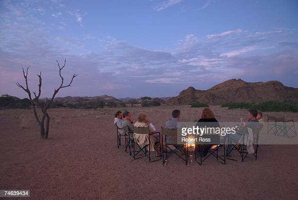tourists on a desert safari sitting around a camp fire - night safari stock pictures, royalty-free photos & images
