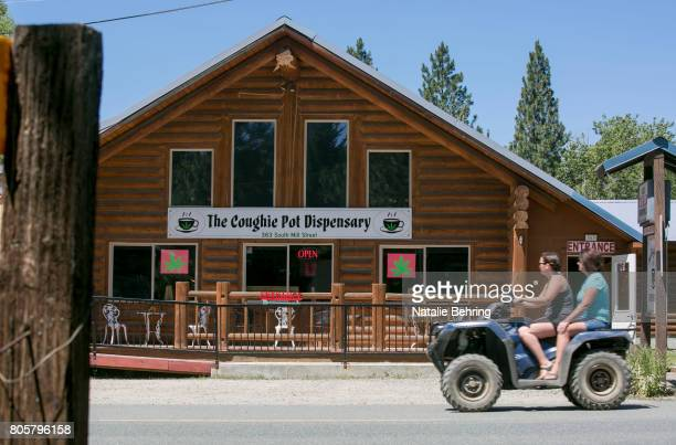 Tourists on a fourwheel leisure vehicle pass the Coughie Pot marijuana dispensary July 2 2017 as they visit the small historical gold mining town of...
