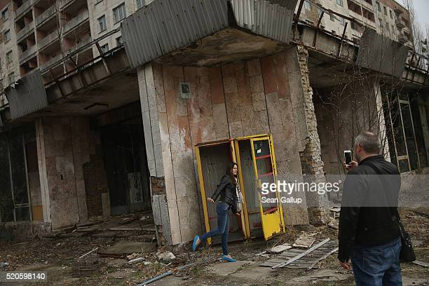 Tourists on a guided tour snap photos of one another outside an abandoned shop and apartment building on April 9 2016 in Pripyat Ukraine Pripyat...