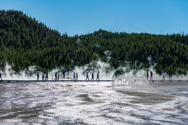 Tourists on a jetty in the thermal area, steaming hot spring, Grand Prismatic Spring, Midway Geyser Basin, Yellowstone National Park, Wyoming, USA