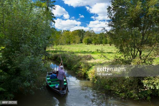 Tourists on barge punting along canal by Coulon in the Marais Poitrevin region a Grand Site de France.