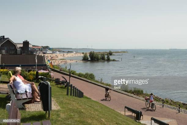 tourists on bench overlooking ijsselmeer on sunny summer day - flevoland stockfoto's en -beelden