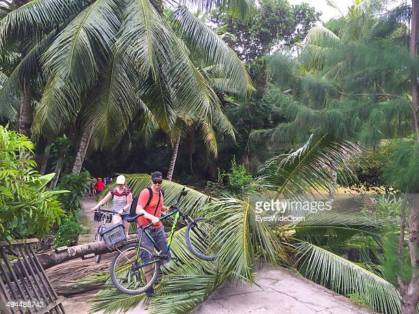 Tourists on bicycles have to overcome a overturned palmtree near famous Source D´Argent beach on September 22 2015 in La Passe La Digue Seychelles