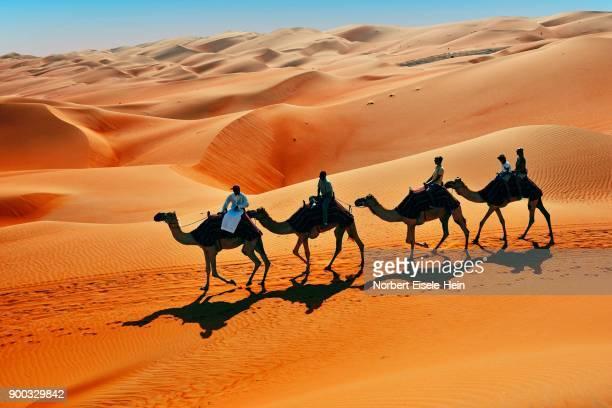 Tourists on camel ride in front of high sand dunes, sandy desert, Rub Al Khali, Emirate of Abu Dhabi, United Arab Emirates