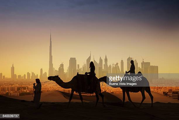 tourists on camels watching a futuristic city - dubai stockfoto's en -beelden