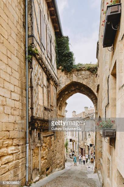 tourists on cobbled street with medieval buildings, saint-emilion, aquitaine, france - aquitaine stock photos and pictures