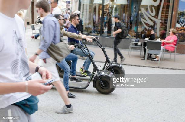 tourists on electric scooter in street of downtown of budapest during summer day - mobility scooter stock photos and pictures