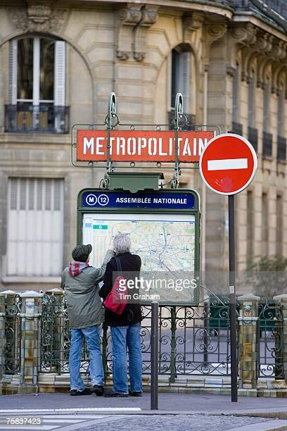Tourists on foot study Metropolitain subway map for the Paris Metro in Rue du Bac Left Bank Paris France