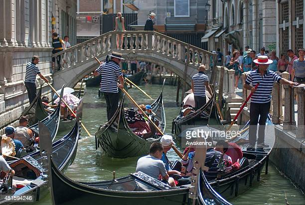 Tourists on gondolas sail in the Saint Mark's area on July 22 2015 in Venice Italy With an estimated number of 27 million visitors per year the...