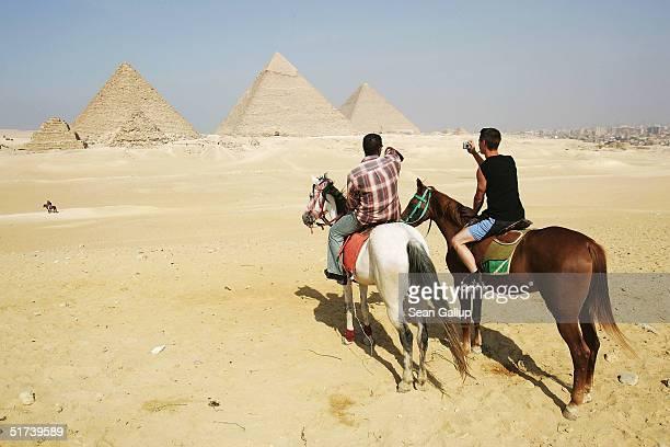 Tourists on horseback marvel at the three large pyramids of Menkaure Khafre and Khufu November 13 2004 at Giza just outside Cairo Egypt The three...