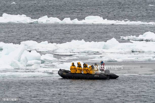 Tourists on inflatable boats exploring the Polar Ice Cap, 81north of Spitsbergen, Norway..
