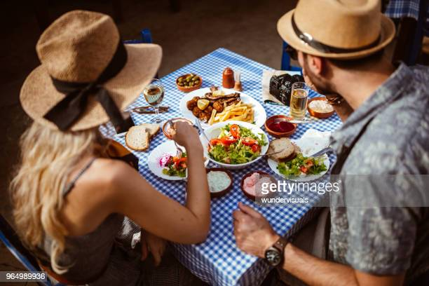 young tourists couple eating traditional greek food at rustic restaurant - cyprus island stock pictures, royalty-free photos & images