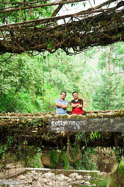 Tourists on old bridges made of vines. India rainforest.