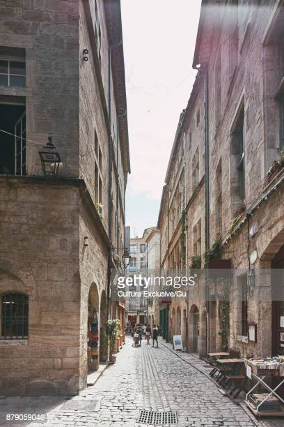 tourists on old town cobbled street, pezenas, occitanie region, france - pezenas stock photos and pictures