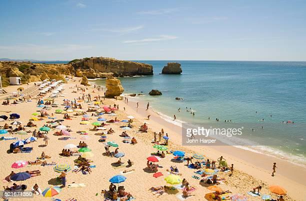 tourists on praia de san raphael in portugal - アルブフェイラ ストックフォトと画像