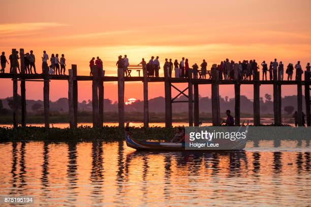 Tourists on row boat with silhouette of people walking along U Bein Bridge across Taungthaman Lake at sunset, Amarapura, Mandalay, Myanmar
