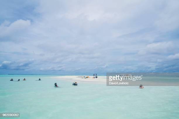 tourists on sand bank like hart near maffushi island on maldives - hart island stock pictures, royalty-free photos & images