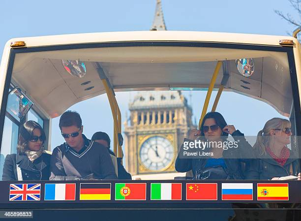 Tourists on sightseeing bus in London with Big Ben clock face in the background