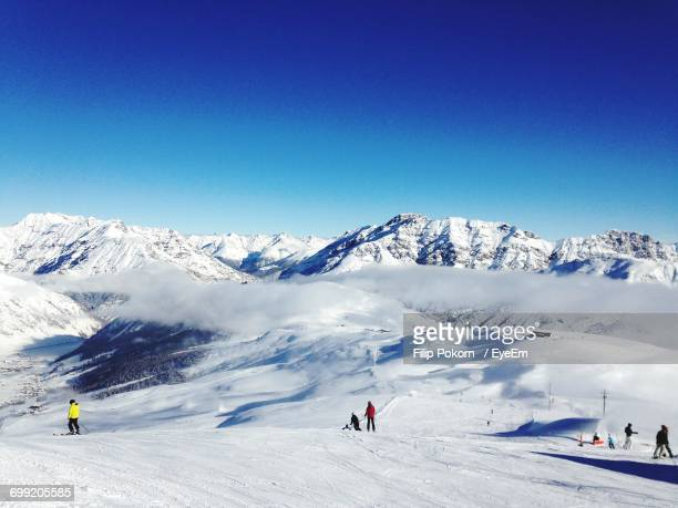 Tourists On Snow Covered Mountain Against Clear Sky