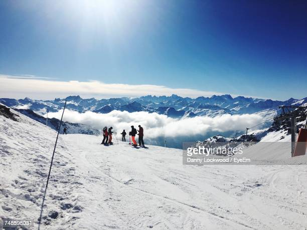 tourists on snow covered mountain - ski holiday stock photos and pictures