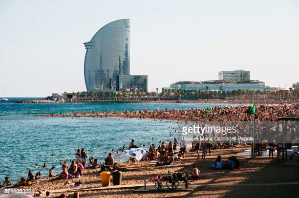 Tourists on the Barceloneta beach in summer with Hotel W Barcelona at back