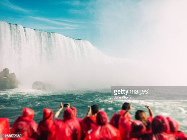 tourists on the boat looking at niagara falls - niagara falls stock pictures, royalty-free photos & images