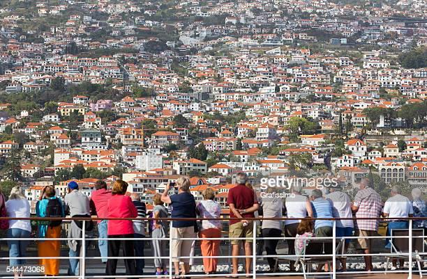 Turistas sobre o cruzeiro navio MSC Poesia a olhar para Funchal