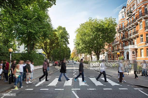 tourists on the iconic abbey road zebra crossing - cruzar fotografías e imágenes de stock