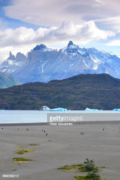 Tourists on the shore of Lake Grey with ice floes, Los Cuernos massif in the background, Torres del Paine National Park, Ultima Esperanza Province, Chile