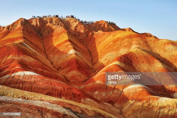 tourists on the stand to see the beautiful scenery of danxia landform  in the national geopark of zhangye, gansu, china. - unesco stock pictures, royalty-free photos & images