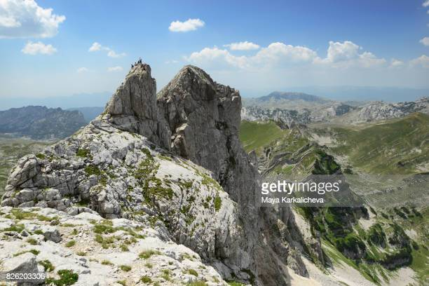 Tourists on top of a rocky peak in Durmitor mountain