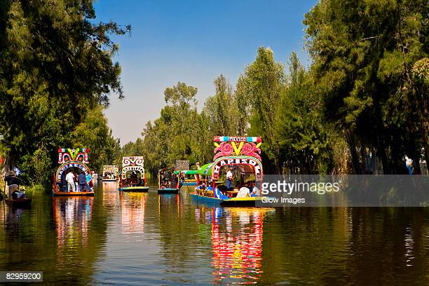 tourists on trajineras boats in a canal, xochimilco gardens, mexico city, mexico - mexico city stock pictures, royalty-free photos & images