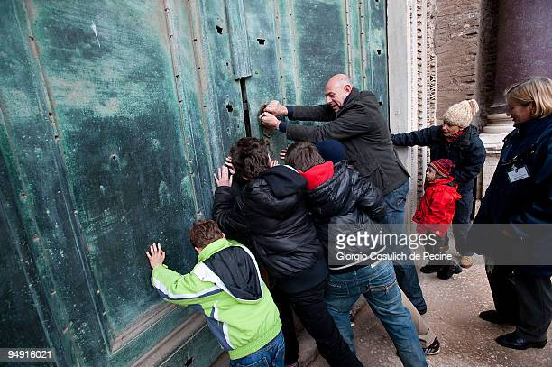 Tourists open the original main door of the Romolo's Temple in the archaeological area of the Roman Forums which opens to the public for the first...