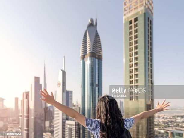 tourists open their arms and look forward to the city of dubai - look back at early colour photography imagens e fotografias de stock