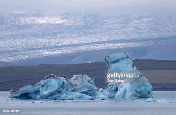 Tourists paddle kayaks past an iceberg that has broken off of receding Breidamerkurjokull glacier, which looms behind, on Jokulsarlon lake on August...