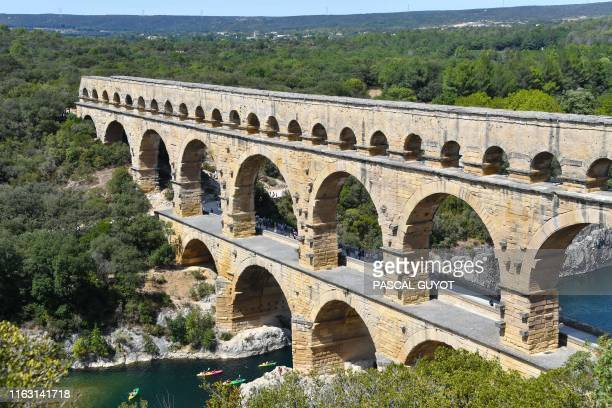Tourists paddle kayaks under the Pont du Gard, a Roman aqueduct bridge part of the UNESCO's list of World Heritage Sites, on August 21, 2019 in...