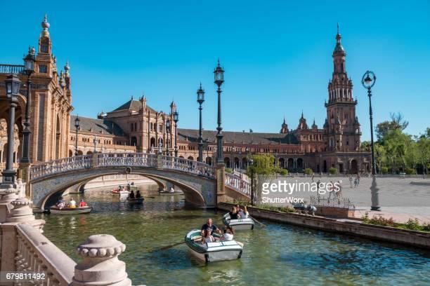 os turistas remem botes no canal em torno dos edifícios na plaza de españa em andaluzia espanha sevillia - lugar histórico - fotografias e filmes do acervo