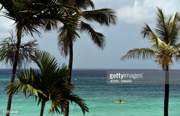 Tourists paddles by near a beach in Bridgetown, Barbados on May 4, 2015. AFP PHOTO/JEWEL SAMAD