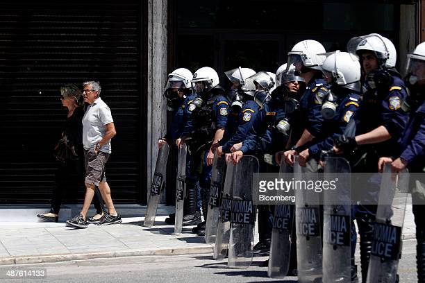 Tourists pass a line of Greek riot police as they watch May Day protests in Athens Greece on Thursday May 1 2014 Greece's successful return to bond...