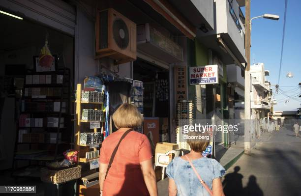 Tourists pass a local supermarket on the way to the sea in Hersonissos, on the island of Crete, Greece, on Tuesday, Sept. 24, 2019. Like Crete,...