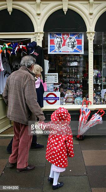Tourists pass by a commerative teatowel hanging in a gift shop window near Windsor Castle and the Guildhall 30 March 2005 Prince Charles is to marry...