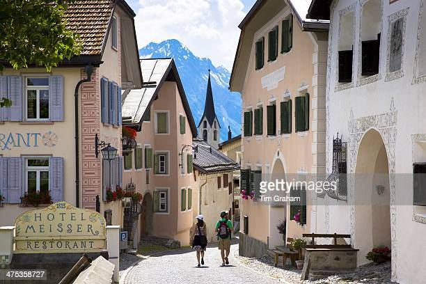 Tourists pass Hotel Meisser in Engadine Valley village of Guarda painted stone 17th Century buildings Switzerland