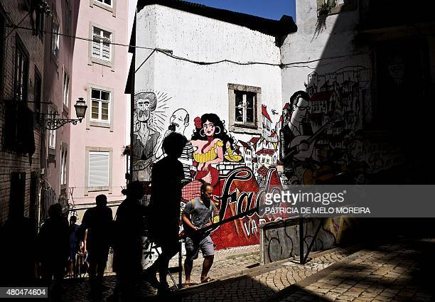 Tourists pass in front of a graffiti representing the history of Portuguese best known music genre the Fado at Sao Cristovao stairs in Lisbon on July...