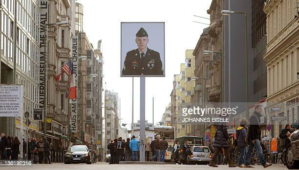 Tourists pass the former Allies' checkpoint at Checkpoint Charlie in Berlin on October 24 2011 where a plaque commemorates the 50th anniversary of...