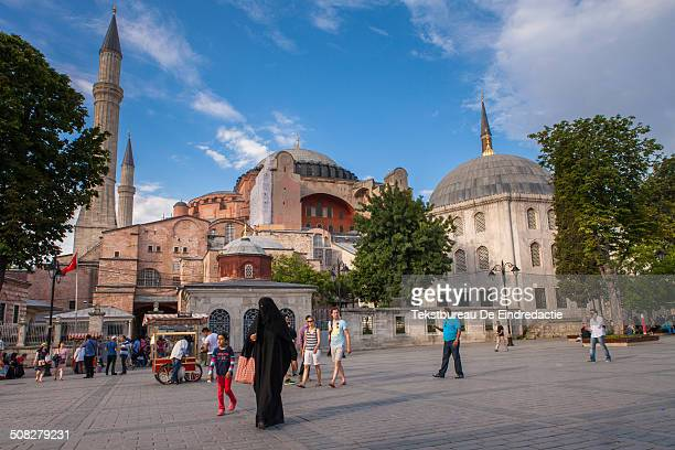 CONTENT] Tourists passing in front of the Hagia Sophia museum late in the afternoon under a blue sky with white clouds