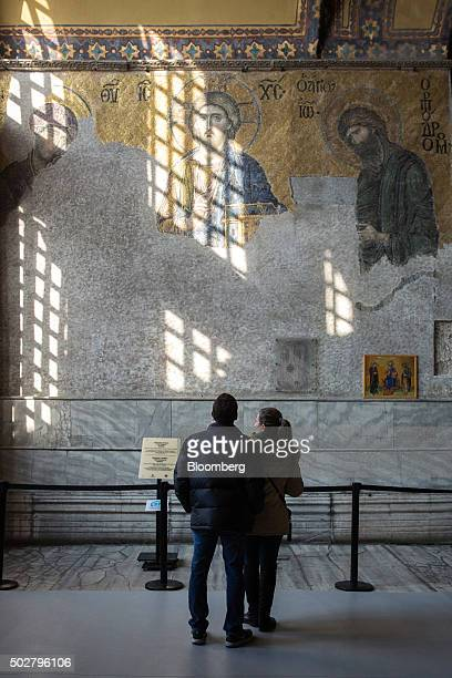 Tourists pause to look at an ancient mosaic on the wall of the Hagia Sophia mosque in the Sultanahmet district of Istanbul, Turkey, on Tuesday, Dec....