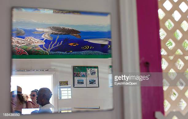 Tourists peopleand a indigenous women are reflected in a mirror of a bahamian restaurant on June 15 2012 in Cat Island The Bahamas