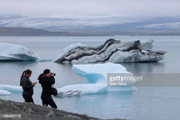 Tourists photograph icebergs that have broken off of receding Breidamerkurjokull glacier, which looms behind, at Jokulsarlon lake on August 15, 2021...