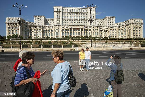 Tourists photograph one another in front of the Palace of the Parliament built by former Romanian dictator Nicolae Ceausescu on September 7 2013 in...