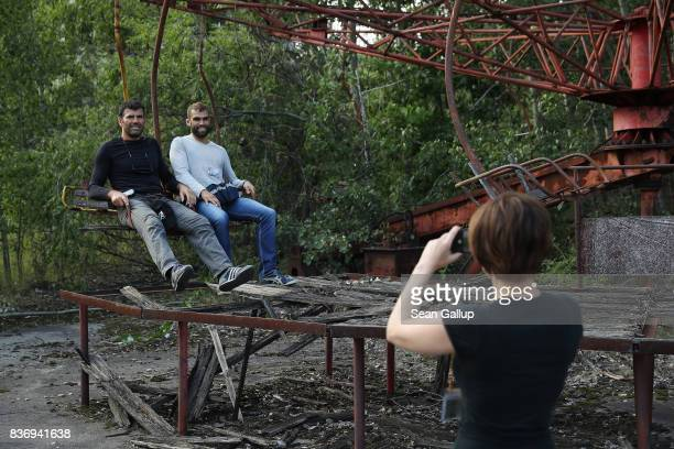 Tourists photograph one another on the remains of a merry-go-round in the ghost town of Pripyat not far from the Chernobyl nuclear power plant on...